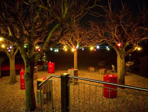 Außenbereich im Winter bei Nacht mit Lichterketten